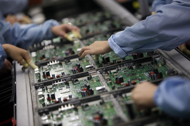Celestica employees work at a production line in a factory in Dongguan, China's southern Guangdong province, July 29, 2009. Contract electronics manufacturer Celestica Inc reported a lower second-quarter profit last Thursday, partly due to costs related to job cuts, and said it planned to spend more on restructuring this year. REUTERS/Tyrone Siu (CHINA BUSINESS POLITICS)
